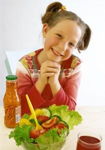 Junges Maedchen sitzt vor Salatschuessel